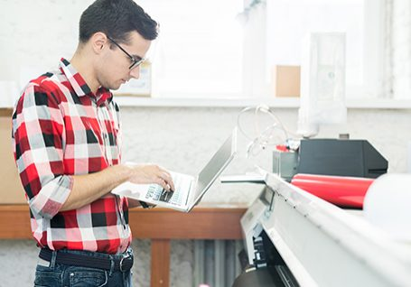 Tech-With-Laptop-Standing-At-Printer-Image